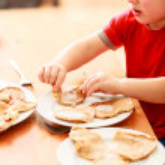 Little boy eating apple pancakes — Stock Photo #56508111
