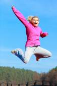 Cheerful woman in tracksuit jumping — Stock Photo