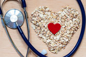 Oat flakes heart shaped and stethoscope — Stock Photo