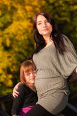 Pregnant woman with daughter in park — Stock Photo