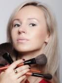Woman holds makeup brushes — Stok fotoğraf