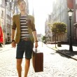 Young handsome man with suitcase on street — Stock Photo #57122609