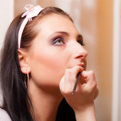 Makeup artist applying lipstick on lips — Stockfoto