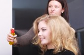 Hairstylist appies hairspray — Stock Photo