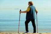 Aktive frau senior-nordic-walking am strand — Stockfoto