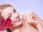 Young woman applying moisturizing cream — Stock Photo