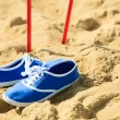 Nordic walking. sticks and violet shoes on a sandy beach — Stock Photo #58230997
