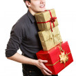 Young man holding gifts — Stock Photo #58231581