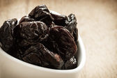Prunes in white bowl on wooden table — Stock Photo