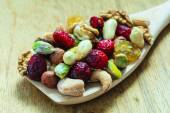Varieties of dried fruits and nuts on wooden spoon. — Stock Photo