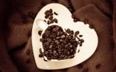Corazón en forma de taza con granos de café en café — Foto de Stock