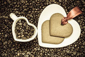 Heart shaped cup and cookie on coffee beans background — Stock Photo