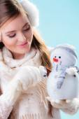 Woman in warm clothes holding snowman toy. — Stock Photo