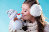 Woman in warm clothes holding snowman toy. — Foto de Stock