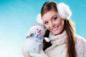 Woman in warm clothes holding snowman toy. — Stock fotografie