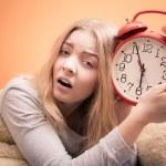 Girl in bed holds alarm clock — Stock Photo #59135643
