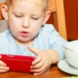 Boy drooling eating breakfast playing with mobile phone — Stock Photo #59920203