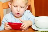 Boy drooling eating breakfast playing with mobile phone — Stock Photo