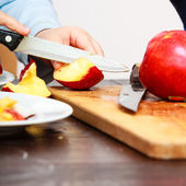 Child cutting apple — Stock Photo