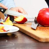 Child cutting apple — Stock Photo