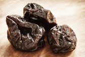 Prunes on wooden table — Stock Photo