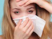 Girl sneezing in tissue. — Stock Photo