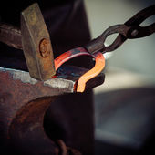Blacksmith forges hot horseshoe. — Stock Photo