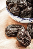Dried plums prunes on wooden table — Stock Photo