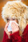 Sick woman sneezing in tissue outdoor — Stock Photo