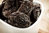 Dried plums prunes in white bowl on wooden table — Stock Photo