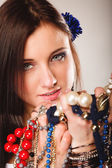Summer girl with plenty of jewellery, beads in hands — Stock Photo
