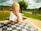 Child playing draughts or checkers board game outdoor — Stock Photo