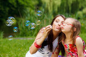 Mother blowing soap bubbles — Stock Photo