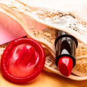 Condom and red female lipstick — Stock Photo