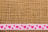 Pink heart ribbon on cloth — Stockfoto
