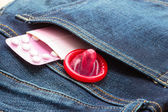 Pills and condom in pocket. — Stock Photo
