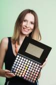 Woman holding makeup  palette — Stock Photo