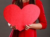 Girl holding heart in hands — Stock Photo