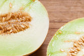 Melon with pips on wooden table. — Stock Photo