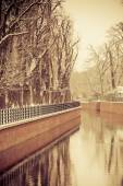 Park with river and embankment covered with snow — Stockfoto