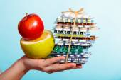 Hand holding pills and fruit — Stock Photo