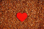 Flax seeds and red heart — Stock Photo