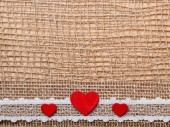 Red hearts on abstract cloth — Stock Photo