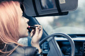 Girl  doing make up while driving the car. — Stock Photo