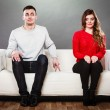 Shy woman and man sitting on sofa — Stock Photo #66235995