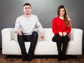 Shy woman and man sitting on sofa — Stock Photo