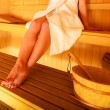 Woman sitting relaxed in wooden sauna — Stock Photo #67541347