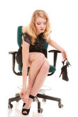 Tired woman sitting on chair and massaging feet — Stock Photo