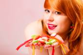 Red haired woman holding candies — Stock Photo