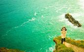 Irish atlantic coast. Woman tourist standing on rock cliff — Stock Photo